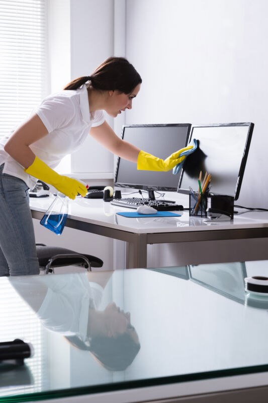Woman Janitor Lady Cleaning Desk In Office